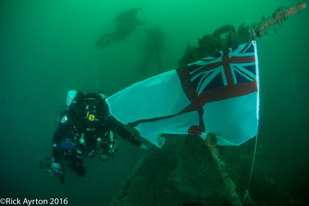 Ian Taylor with the white ensign he has just tied onto the anti aircraft gun